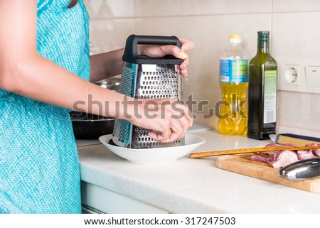 Woman grating cheese on a grater to use as an ingredient in her cooking as she prepares a meal - stock photo