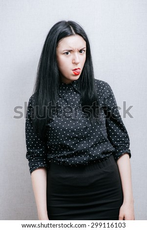 Woman grimace on her face showing tongue. On a gray background. - stock photo