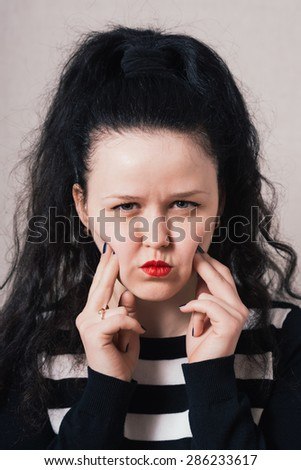 Woman grimacing. Gray background - stock photo