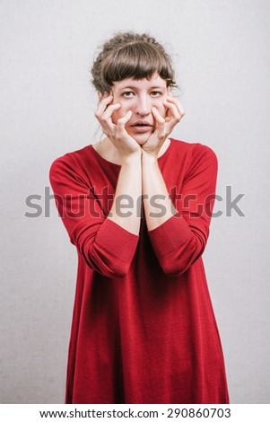 Woman grimacing, hands on his cheeks. On a gray background. - stock photo
