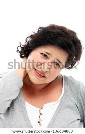 Woman grimacing in pain as she rubs her neck Woman grimacing in pain as she rubs her painful neck after her muscles have contracted in a tension spasm - stock photo
