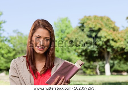 Woman grinning while looking straight ahead with a book in her hands in a sunny grassland area - stock photo