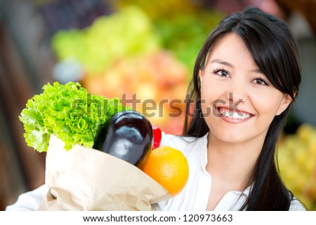 Woman grocery shopping and looking very happy - stock photo