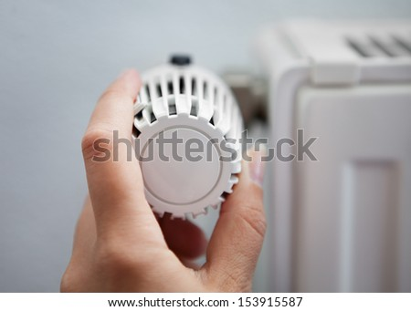 Woman Hand Adjusting The Temperature By Thermostat - stock photo