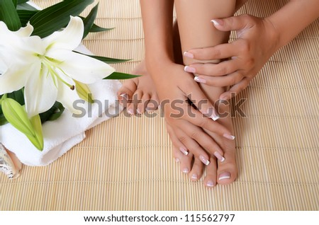 Woman hand and feet with manicure and  Lily - stock photo