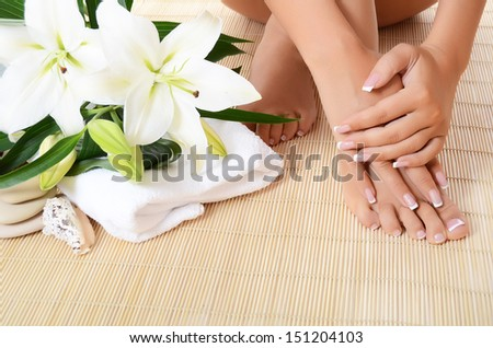 Woman hand , feet with manicure and Lily - stock photo