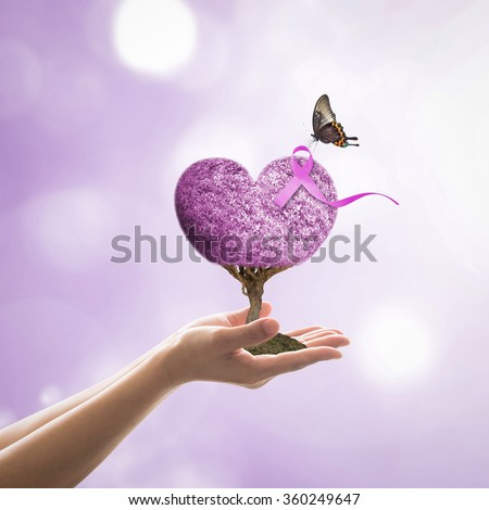Woman hand giving lavender purple color heart shape love living tree life w/ symbolic ribbon & butterfly blur background: Cancer awareness (all kinds) concept raising support people living w/ illness - stock photo