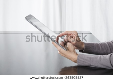 woman hand grey sweater finger touching digital tablet blank screen on black reflect table white curtain indoor - stock photo