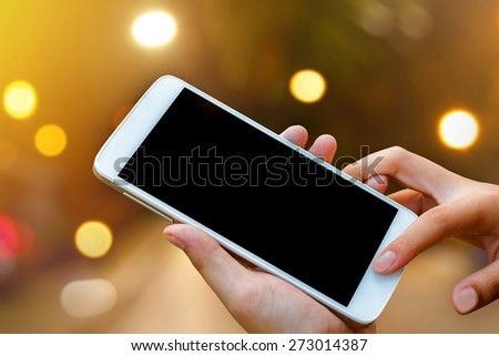 woman hand hold and touch screen smart phone, tablet,cellphone on abstract blurred bokeh of city night light background background. - stock photo