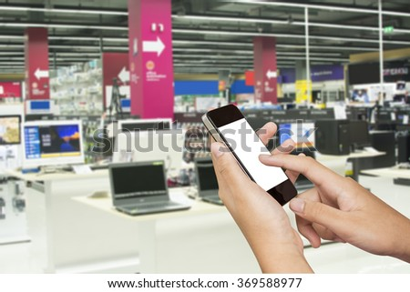 woman hand hold and touch screen smart phone, tablet,cellphone over computer store - stock photo
