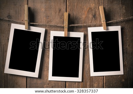 Woman Hand Hold Blank Old Photo Frame Hanging on a Rope By Clothespin  - stock photo
