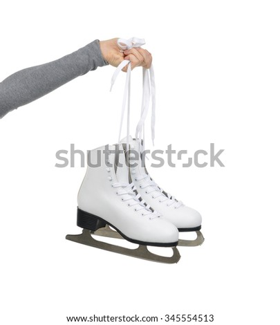 Woman hand hold ice skates isolated on a white background - stock photo