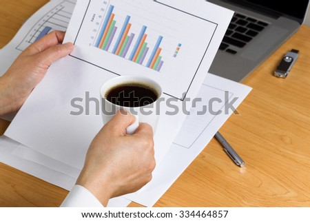 Woman hand holding a cup of dark coffee while looking over financial data with printed graphs, partial laptop, pen and thumb drive on desktop. - stock photo