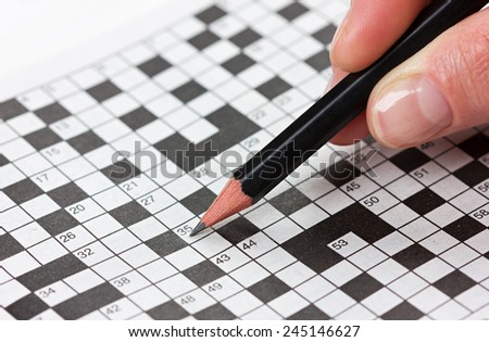 woman hand holding a pencil and solves crossword puzzle - stock photo