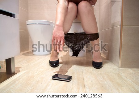 woman hand holding a phone in the toilet floor - stock photo