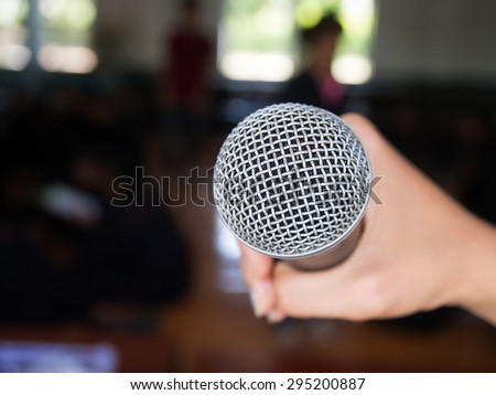 Woman hand holding a silver microphone aiming to the empty space on the left with de-focused people  in background . - stock photo
