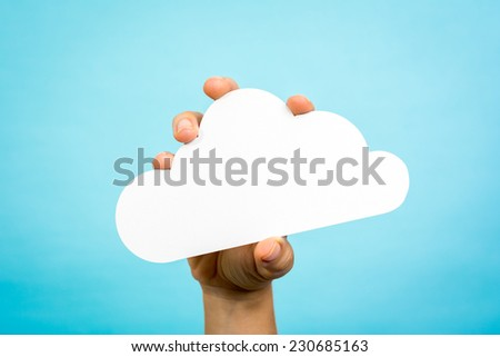 Woman hand holding a white paper cloud conceptual on blue background. - stock photo