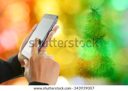 Woman hand holding and touch screen smart phone, over Christmas decorations. - stock photo