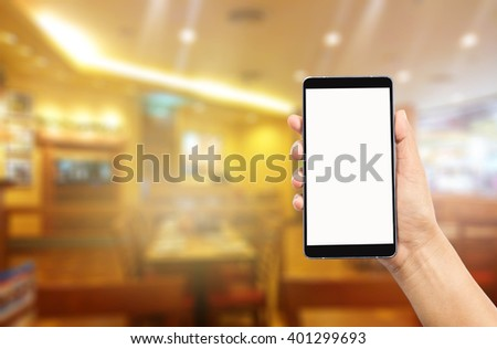 woman hand holding and using mobile over blurred image of restaurant background,Transactions by smart phone concept - stock photo