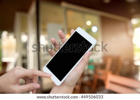 woman hand holding and using mobile (smart phone) blurred image of coffee shop background,Transactions  concept - stock photo