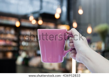 Woman hand holding coffee cup on coffee shop blurred background, stock photo - stock photo