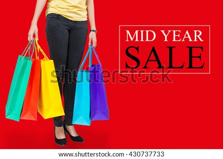 Woman hand holding colorful shopping bags with red background and the word mid year sale. Shopping concept with mid year sale. - stock photo