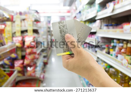 Woman hand holding credit card at convenience store - stock photo