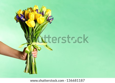 Woman hand holding flowers over green background - stock photo