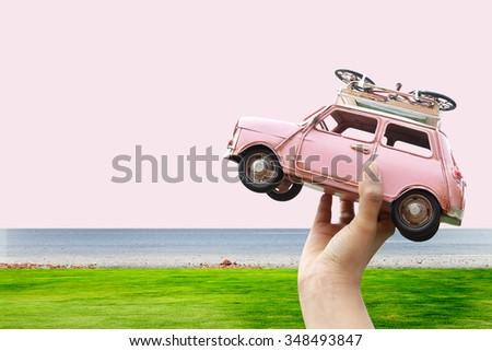 woman hand holding miniature car on white background(travel concept) - stock photo
