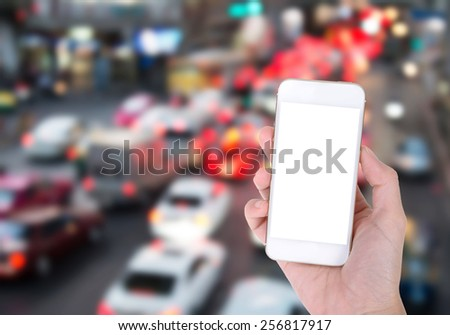 Woman hand holding Mobile Phone with night light traffic jam Background - stock photo