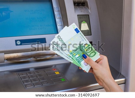 woman hand holding money at an outdoor bank ATM holding a handful of banknotes - stock photo
