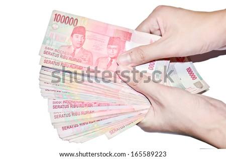 woman hand holding money Indonesia, isolated on white background - stock photo