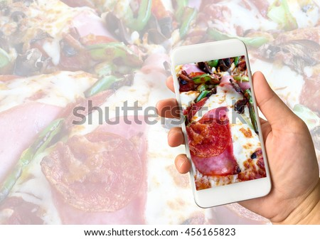 Woman hand holding smartphone against pizza background food online concept - stock photo