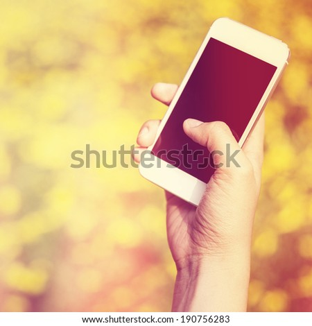 Woman hand holding smartphone against spring green and yellow flowers background - stock photo