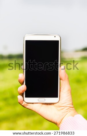 Woman hand holding smartphone against spring green background soft focus. - stock photo