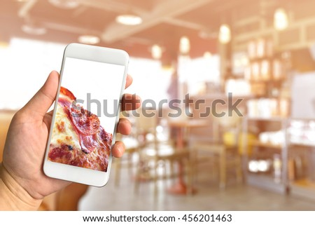 Woman hand holding smartphone pizza with copy space on screen against blurred restaurant background food online concept - stock photo