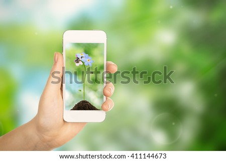 Woman hand holding smartphone with small flower on screen against blur green background - stock photo