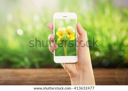 Woman hand holding smartphone with small flowers on screen against blur green background - stock photo