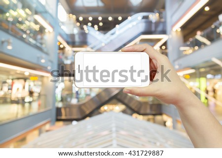 Woman hand holding smartphones with isolated white screen in foods zone on blurred shopping centre background, concepts of online shopping through digital smartphone, mobile or tablet device  - stock photo
