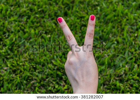 Woman hand holding up the peace sign or number two with two fingers on green grass background texture - stock photo