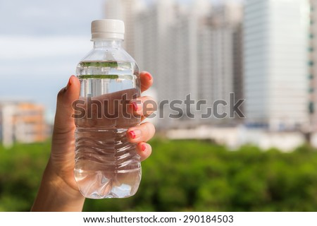 Woman hand holding water bottle against green background - stock photo
