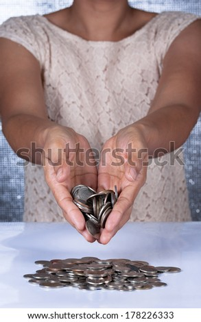 Woman hand inserting a coin into a piggy bank - stock photo