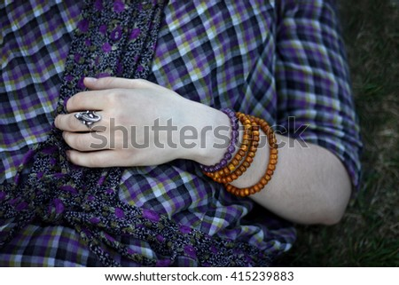 woman hand on grass with lizard ring in retro style blue shirt with lot of bracelets on hands - stock photo