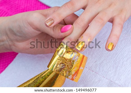 woman hand on manicure treatment with transfer foil in beauty salon - stock photo