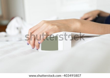 Woman hand on white digital alarm clock in bedroom at morning - stock photo