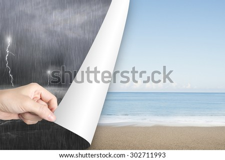Woman hand open calm sea beach page to replace dark stormy ocean - stock photo
