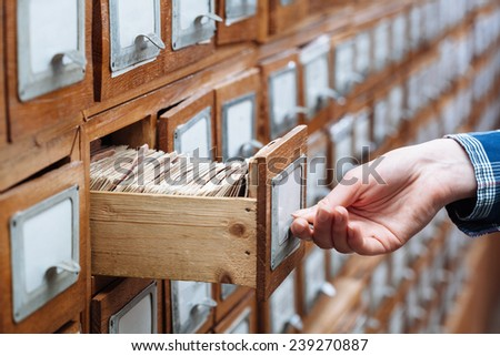 woman hand opening a file cabinet drawer full of files  - stock photo