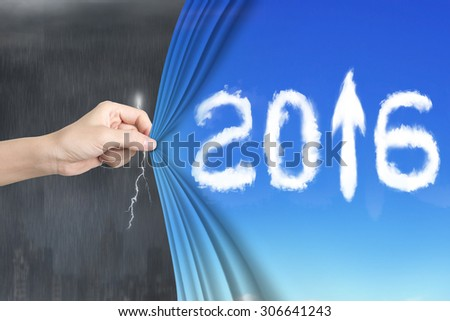 Woman hand pulling open 2016 arrow up curtain covering stormy city. - stock photo