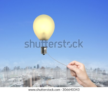 Woman hand pulling rope connected yellow lightbulb shape hot air balloon, with sky urban scene background. - stock photo