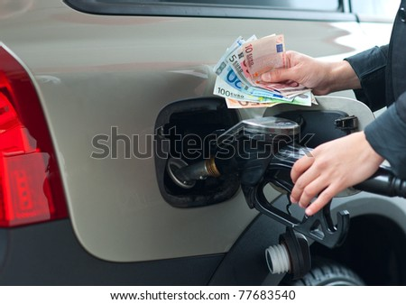 woman hand refuel car holding gas nozzle and money in gas station - stock photo
